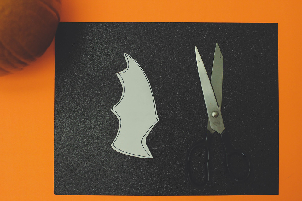 Scissors and a stencil of a batwing placed on black paper.