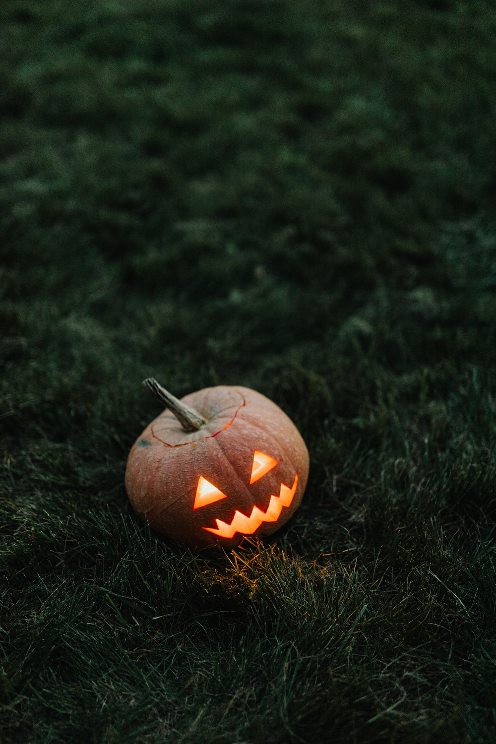 A carved pupkin sitting in the grass.