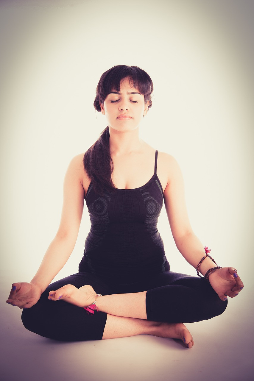 A girl sitting cross legged with her eyes closed.