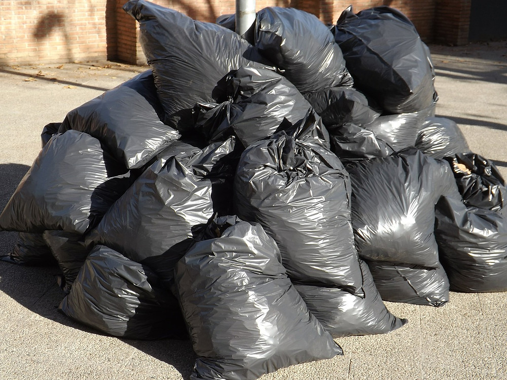 A pile of black garbage bags that are full.