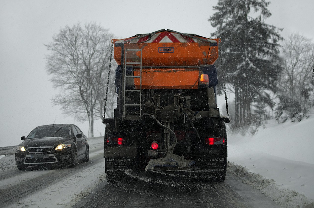 A snow plow salting the streets.