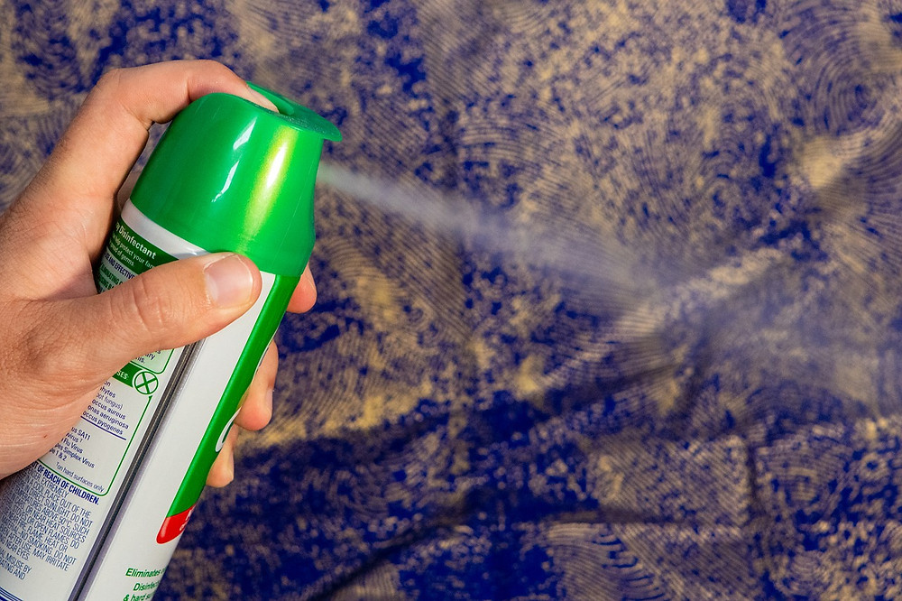 A person spraying a can of cleaner