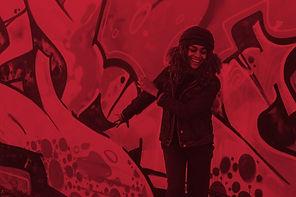 A girl smiling behind a graffiti wall