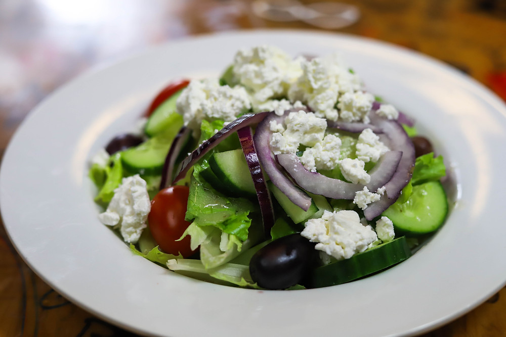 Greek salad with lettuce, onions, tomatoes, olives, and feta cheese.