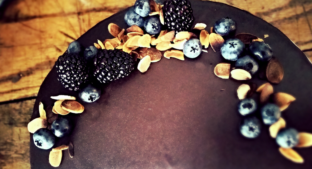 Adorned by a wreath of fresh berries, four layers of dark  chocolate-almond cake, nestled between blackberry buttercream (65%  cacao) and toasted almonds, are enrobed in my signature rum ganache. I made this berry beaut for a friend's birthday party.