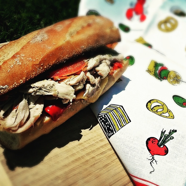 Baguette sandwich with roasted chicken, on a vintage tablecloth