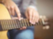 Profesor dando clases de guitarra