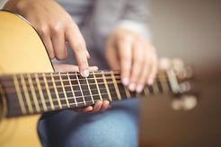 Учитель дает уроки игры на гитаре