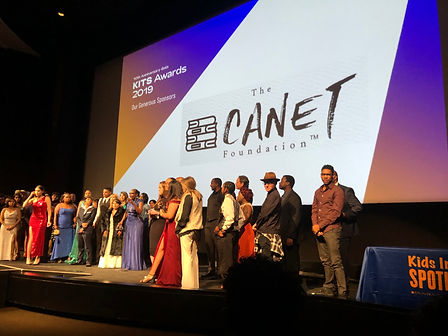 CANET logo on big screen with a bunch of people on stage in front of it.