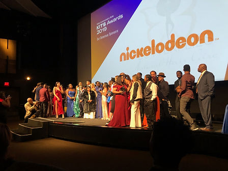 Group of people on stage with the word Nickelodeon on a screen behind them.