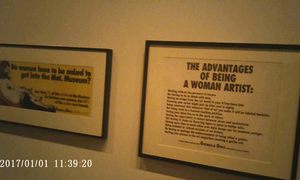 View from my spy glasses of Guerrilla Girls posters at Brooklyn Museum