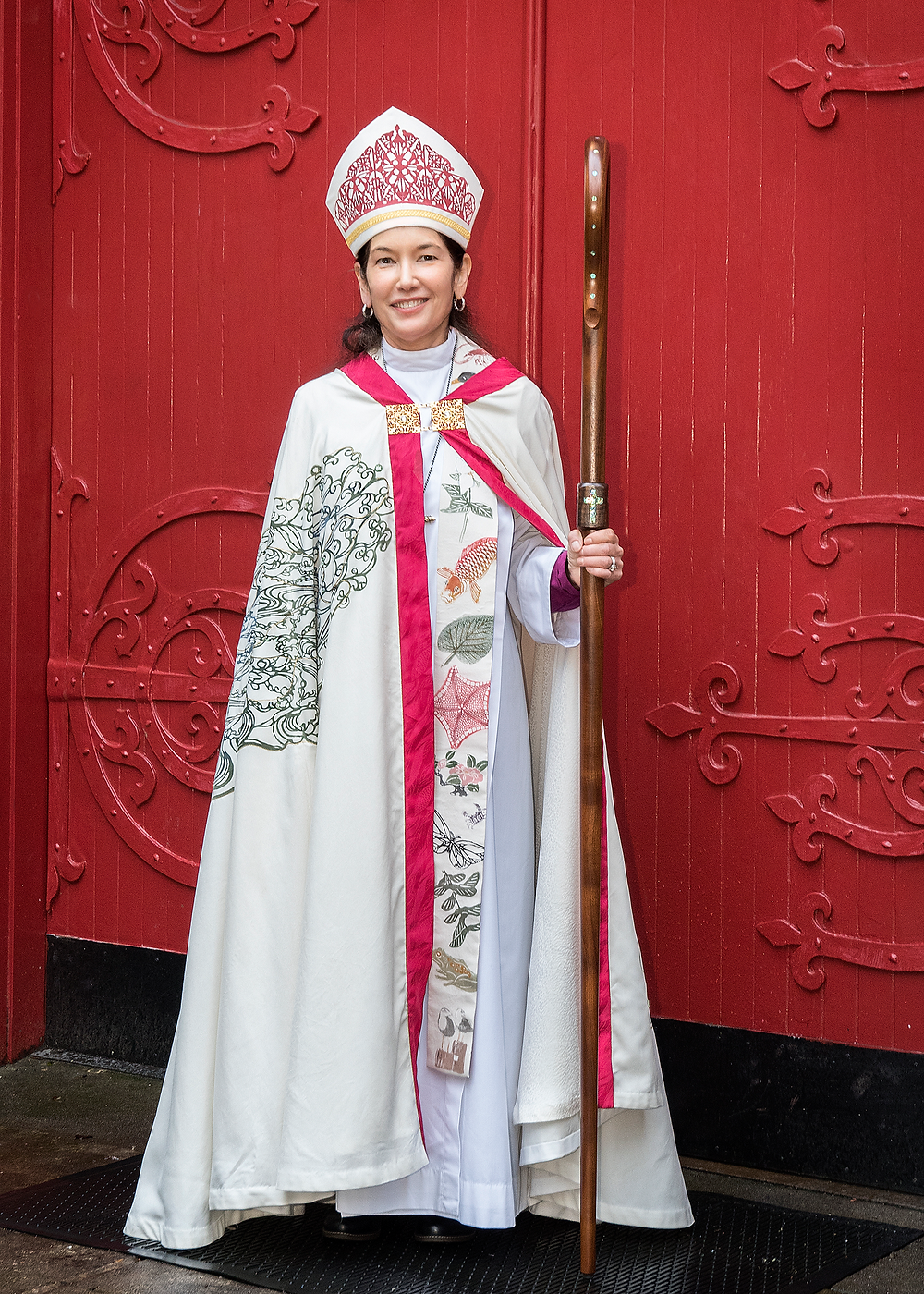 Bishop Akiyama stands in front of a red chapel door at Trinity Episcopal Cathedral in her vestments, holding her crozier.
