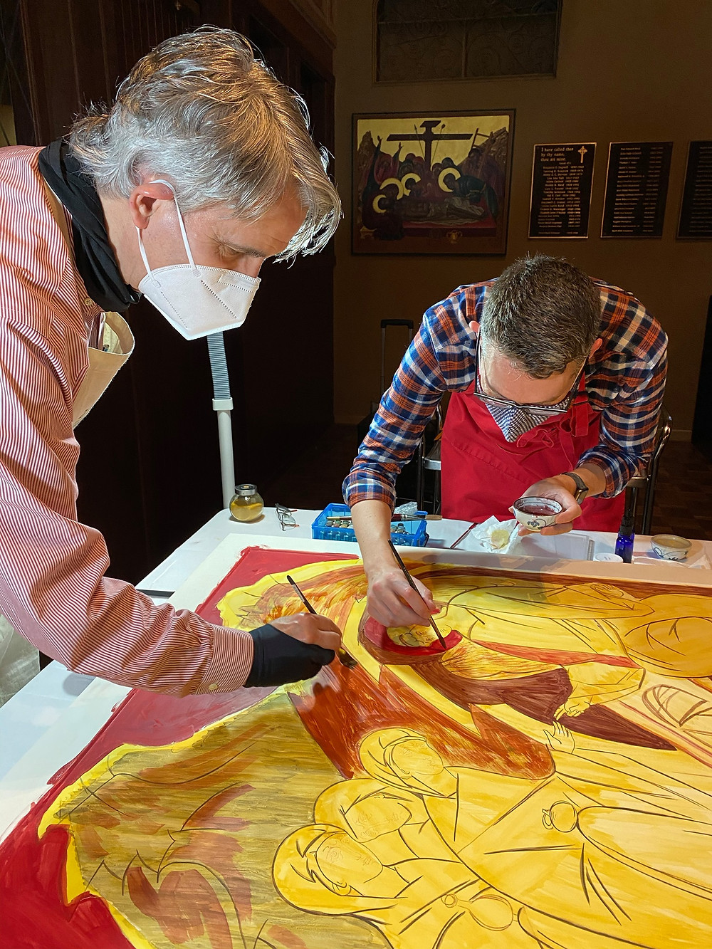 Two men in face masks painting a large horizontal wood icon