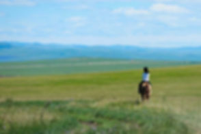 Vast plains Mongolia child rides horse.j