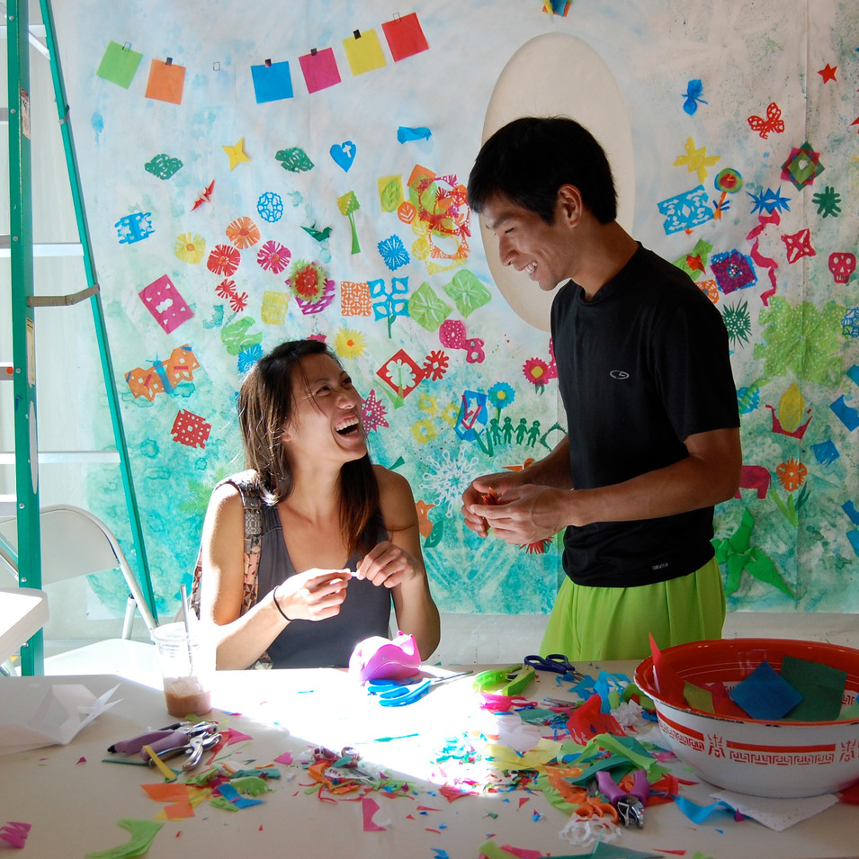 """Visitors create cut paper elements for the """"Community Garden/Nature"""" Panel of the Paper Temple"""
