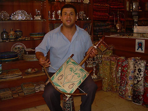Bedouin shopkeeper playing traditional Bedouin instrument, Arab Market, 2009