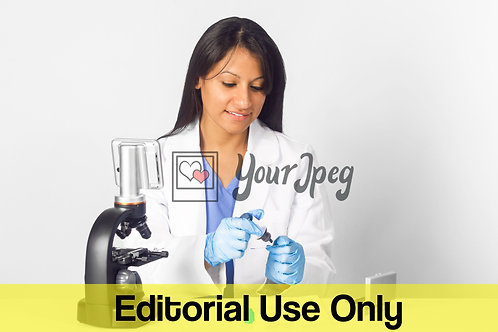 Female Doctor Wearing Gloves While Putting Drops On Microscope Slide