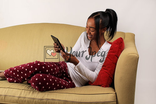 Woman Smiling While Looking Down and Holding Tablet