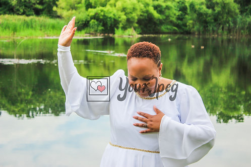 Woman standing by lake raising hand in prayer or thanks to God