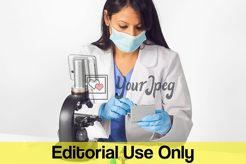 Female Doctor Wearing Mask And Gloves While Using Microscope Equipment #2