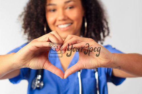 Female Nurse In Scrubs Holding Up Heart Symbol Close Up