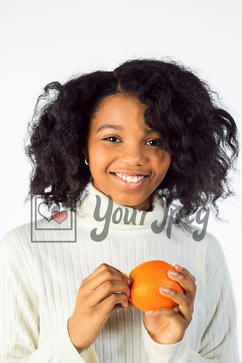 Tween girl smiling with orange