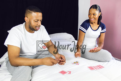 Couple sitting on bed playing cards