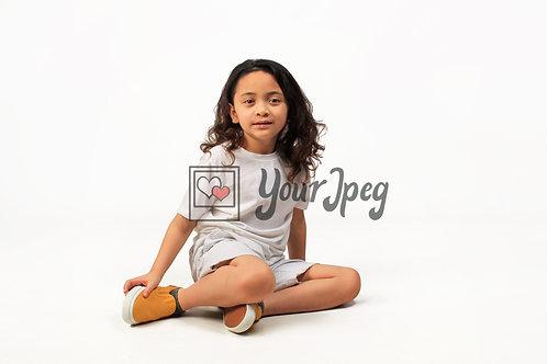 Boy with long hair sitting on floor