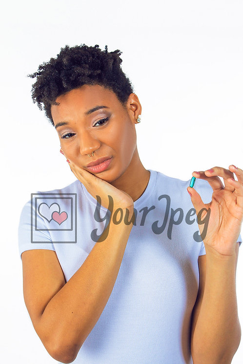 Woman holding chin and pill