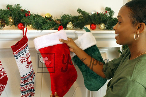 Woman putting up Christmas stocking smiling