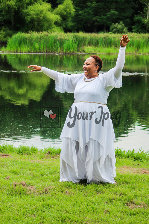 Female praise dancer outdoors with arms up