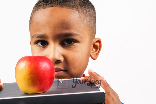 Boy holding a book and apple