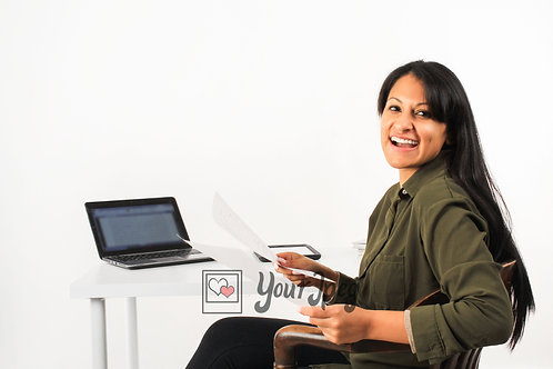 Woman Holding Papers While Sitting At Desk Smiling