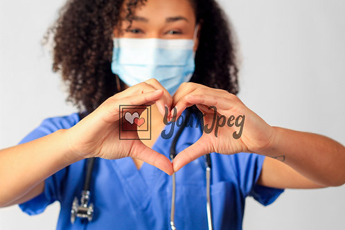 Female Nurse In Scrubs Wearing Mask While Holding Up Heart Symbol