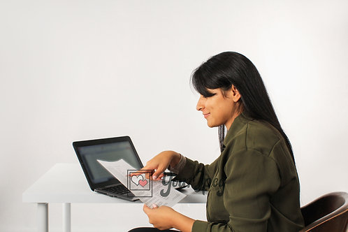Woman Pointing At Paper While Sitting In Front Of Laptop #2