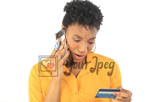 Woman making a call while holding a credit card concerned