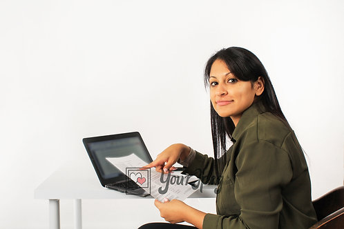 Woman Pointing At Paper While Sitting In Front Of Laptop