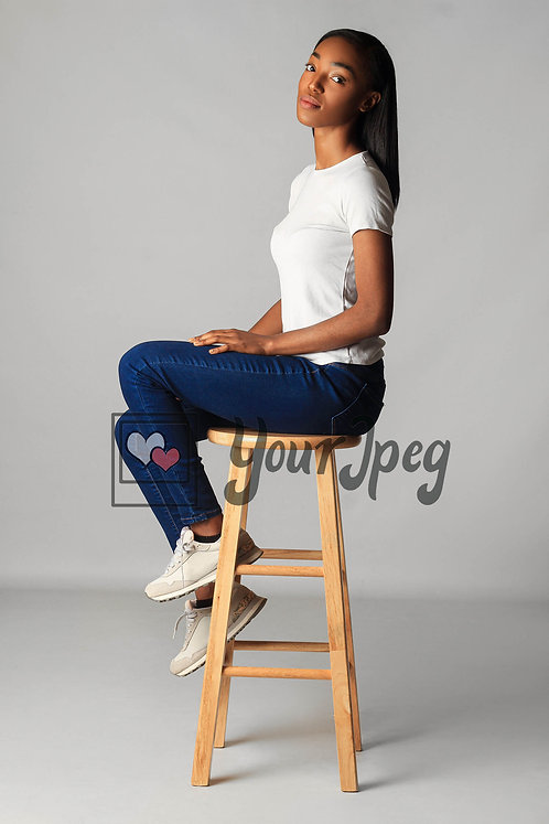 Model Posing While Sitting On Stool At An Angle