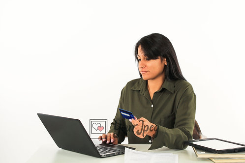 Woman Holding Credit Card While Looking At Laptop