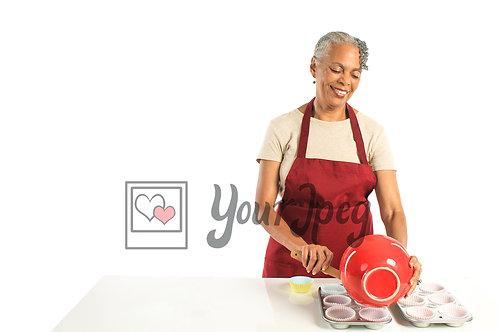 Older woman preparing cupcake batter