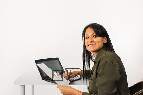 Woman Holding Paper While Sitting In Front Of Laptop Smiling