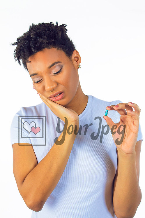 Woman holding chin looking at pill