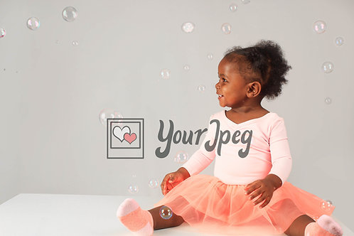 Baby smiling looking at bubbles