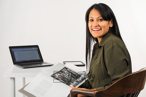 Woman Sitting At Desk Reading Book Smiling