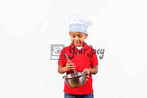 Boy chef looking down into bowl stirring