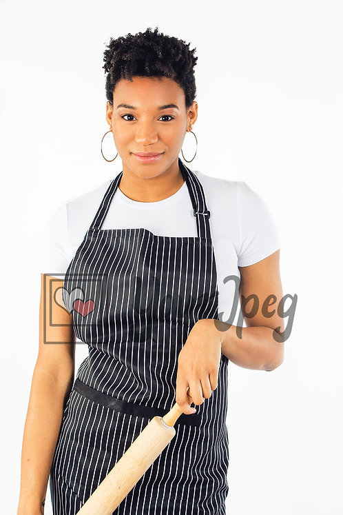 Woman wearing apron while holding rolling pin