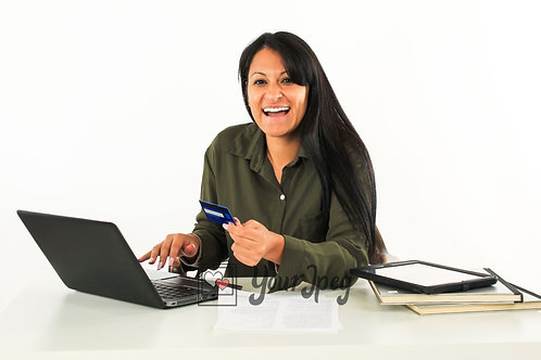 Woman Holding Credit Card While Sitting In Front Of Laptop Smiling