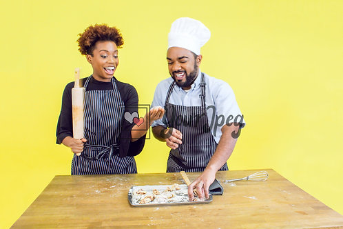 Man and woman prepping for baking and laughing