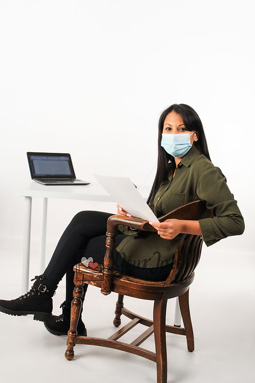 Woman Wearing Mask At Computer Desk Holding Paper