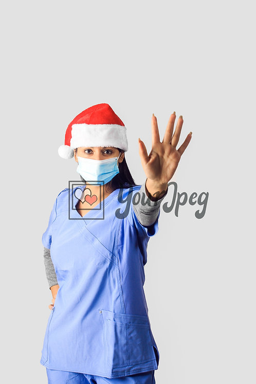 Female Nurse Wearing Christmas Hat And Mask With Stop Hand Signal
